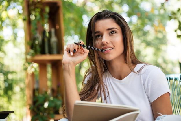 Retrato de una mujer bonita pensativa con libro de texto