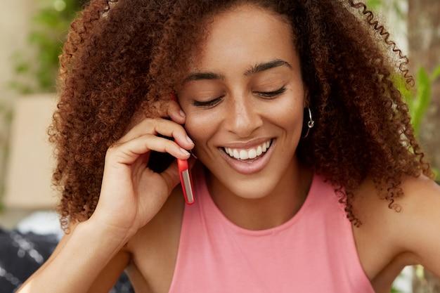 Retrato de mujer bonita de piel oscura con cabello rizado, se ve positivamente hacia abajo, tiene una conversación telefónica agradable con su mejor amigo, comparte impresiones después de tener buenas vacaciones en el extranjero