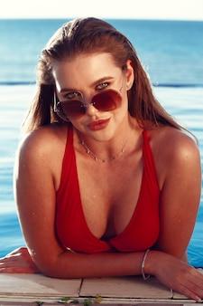 Retrato de mujer bonita en una piscina en vacaciones