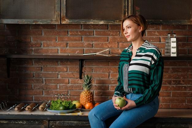 Retrato de una mujer bonita que sostiene la manzana mientras que se sienta en la tabla de cocina.
