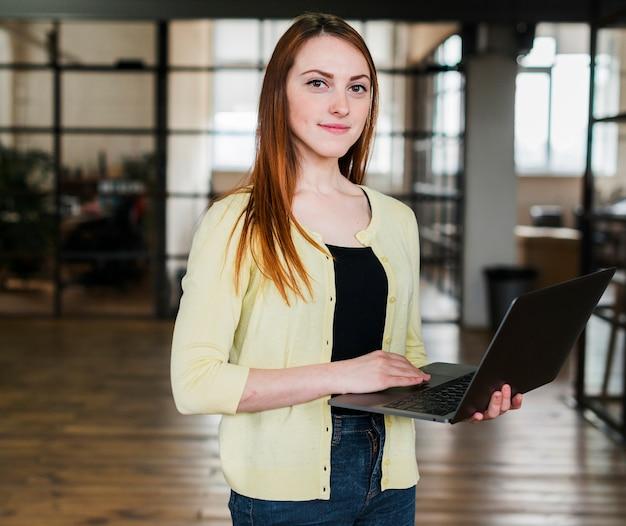 Retrato de la mujer bonita que sostiene el ordenador portátil que mira la cámara