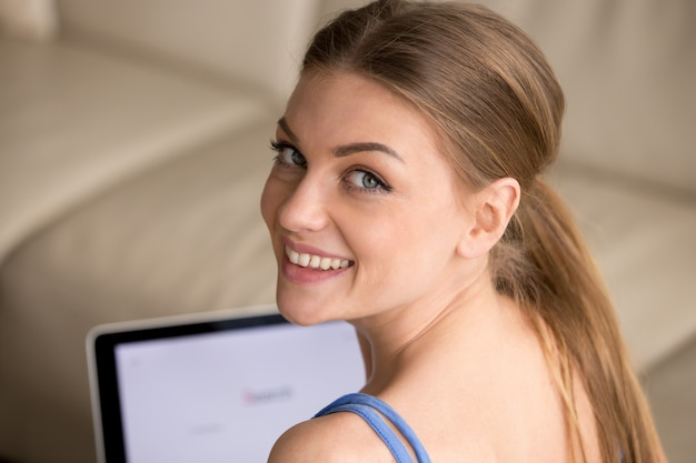Retrato de mujer bonita que trabaja en la computadora portátil en casa