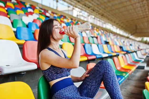 Retrato de una mujer bonita en ropa deportiva sentado y agua potable en el estadio.