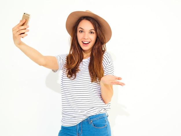 Retrato de una mujer bonita en ropa hipster de verano tomando un selfie aislado en la pared blanca