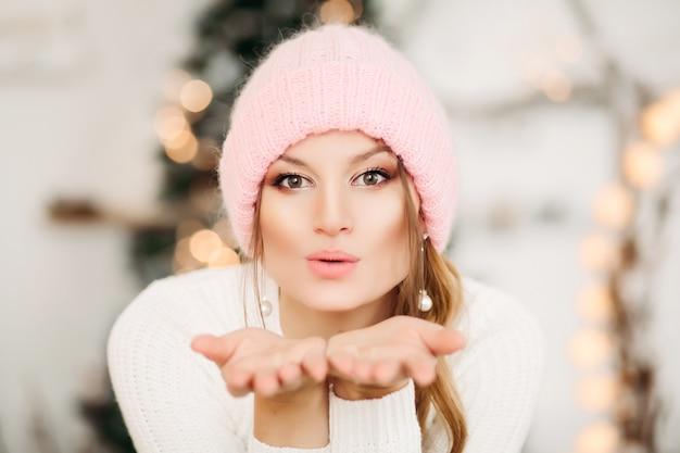 Retrato de mujer bonita rubia en aretes de perlas con sombrero de lana de invierno rosa soplando beso de aire en la parte delantera con las manos, mirando al frente