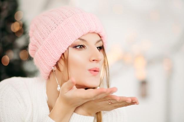 Retrato de mujer bonita rubia en aretes de perlas con sombrero de lana de invierno rosa soplando beso de aire en la parte delantera con sus manos