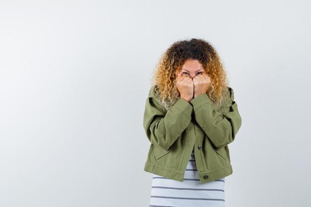 Retrato de mujer bonita rubia escondiendo el rostro detrás de las manos en chaqueta verde y mirando asustado vista frontal