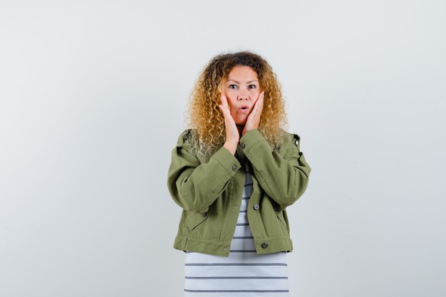 Retrato de mujer bonita rubia manteniendo las manos en las mejillas en chaqueta verde y mirando sorprendido vista frontal