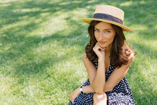 Retrato de mujer bonita vestida con sombrero de verano y vestido de cerca está sentada sobre la hierba en el parque de verano.