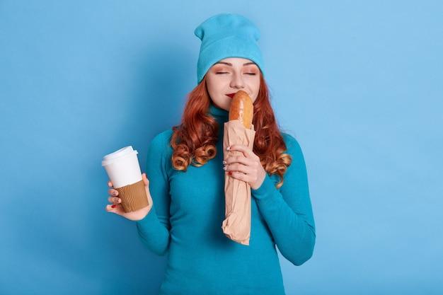 Retrato de mujer bonita vistiendo traje azul oliendo pan largo fresco y sosteniendo café para llevar,