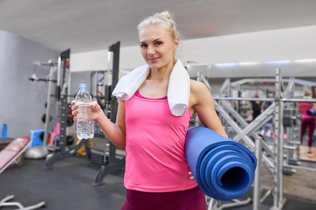 Retrato de mujer con botella de agua y colchoneta deportiva en el club de salud