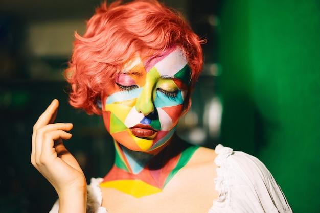 Retrato de una mujer brillante con cabello naranja y maquillaje multicolor