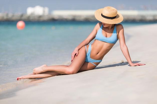 Retrato de mujer bronceada bastante joven sentada en la playa de la isla tropical