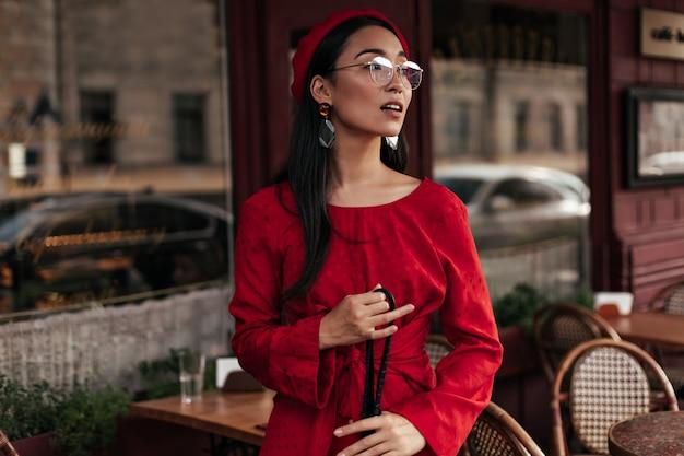 Retrato de mujer bronceada fresca en boina roja, vestido elegante y anteojos sostiene bolso negro y posa afuera