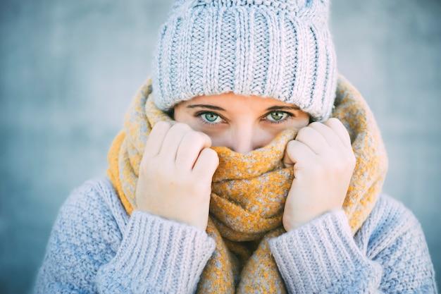 Retrato de mujer en una bufanda y gorra está mostrando que tiene frío.