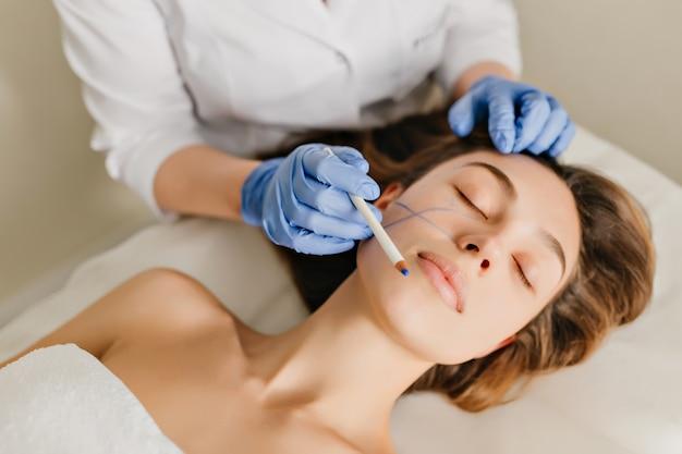 Retrato de mujer con cabello morena en preparación para el rejuvenecimiento, operación de cosmetología en salón de belleza. manos en guantes azules dibujando en la cara, botox, belleza