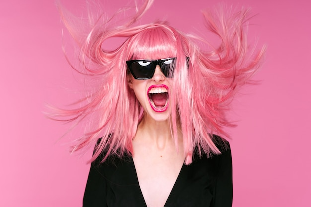Retrato de mujer cabello rosa, pared rosa, gafas y accesorios