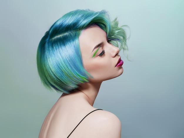 Retrato de una mujer con cabello volador de colores brillantes, todos los tonos de azul violeta. coloración del cabello, maquillaje hermoso.