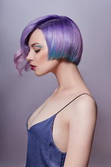 Retrato de una mujer con cabello volador de colores brillantes, todos los tonos de púrpura. tinte de pelo