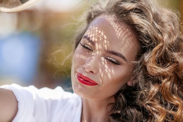 Retrato de una mujer en la calle en un día soleado. chica con una hermosa sonrisa brillante