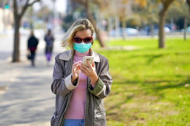 Retrato de mujer en la calle con una máscara médica y habla por teléfono. modelo atractivo infeliz con gripe al aire libre.