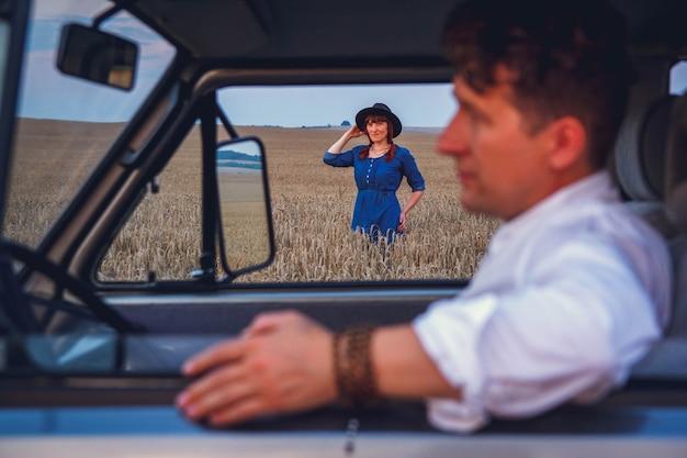 Retrato de mujer caminando por el campo de trigo contra el fondo del cielo y el retrato del hombre que conducía el coche