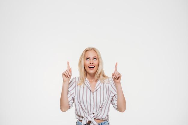 Retrato de una mujer en camisa apuntando dos dedos hacia arriba