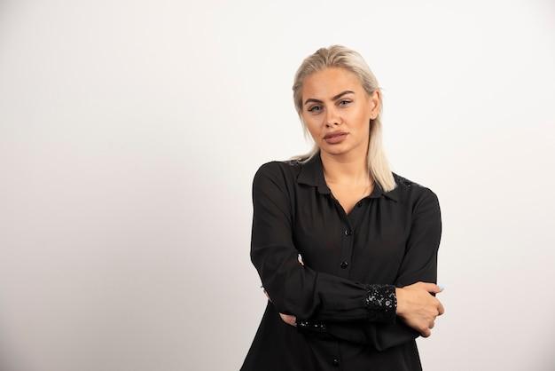 Retrato de mujer con camisa negra posando sobre fondo blanco. foto de alta calidad
