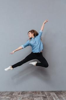 Retrato de mujer en camisa saltando en studio