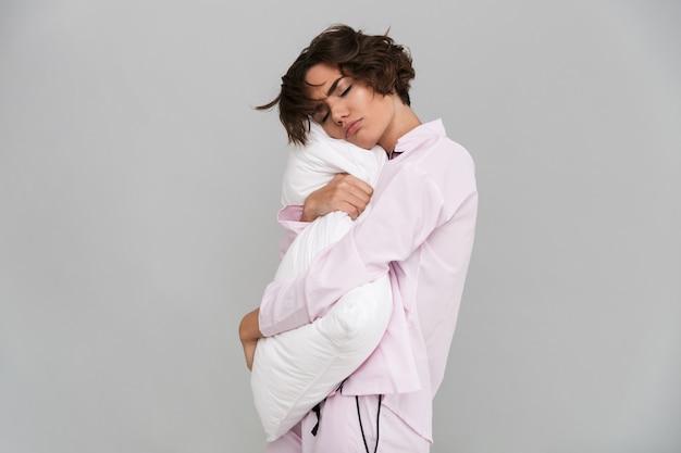 Retrato de una mujer cansada en pijama sosteniendo una almohada