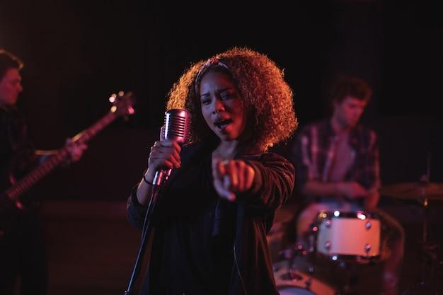 Retrato de mujer cantando en micrófono