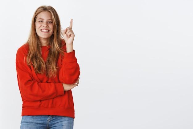 Retrato de mujer carismática despreocupada rembemer broma fresca levantando el dedo índice mientras se ríe y sonríe agregando palabra con gesto eureka dando sugerencia o idea posando en suéter rojo sobre pared gris