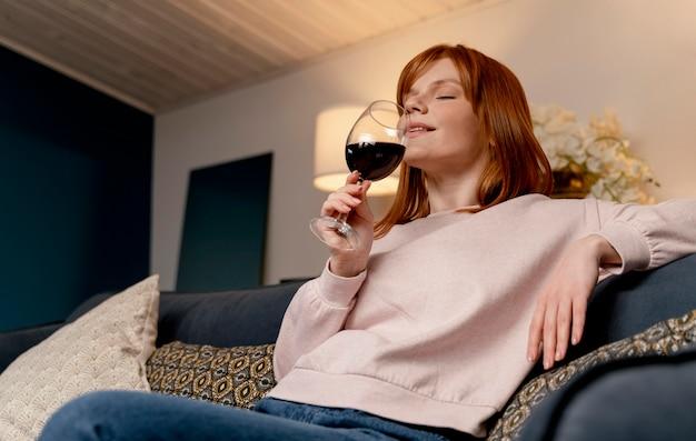 Retrato de mujer en casa relajándose con una copa de vino