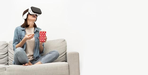 Retrato de mujer con casco de realidad virtual comiendo palomitas de maíz