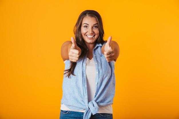 Retrato de una mujer casual joven alegre, mostrando los pulgares para arriba gesto