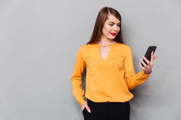 Retrato de una mujer casual mirando la pantalla del teléfono móvil