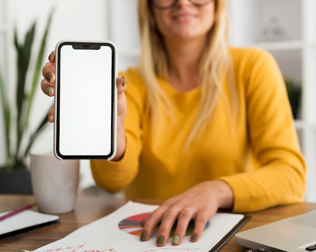 Retrato de mujer casual sosteniendo teléfono móvil