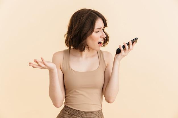 Retrato de mujer caucásica de 20 años disgustada vestida con ropa casual frunciendo el ceño mientras tiene una llamada móvil en un teléfono celular aislado