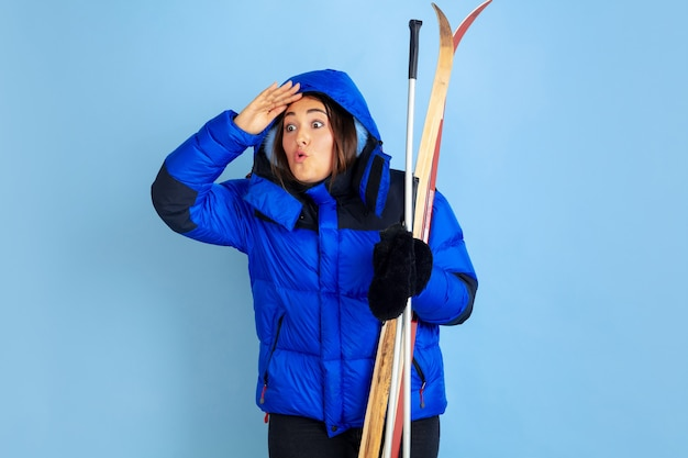 Retrato de mujer caucásica aislado sobre fondo azul de estudio, tema de invierno