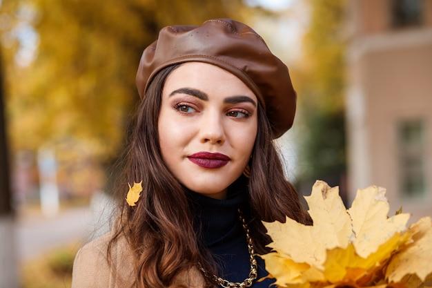 Retrato de mujer caucásica atractiva en otoño. la mujer lleva boina de cuero.
