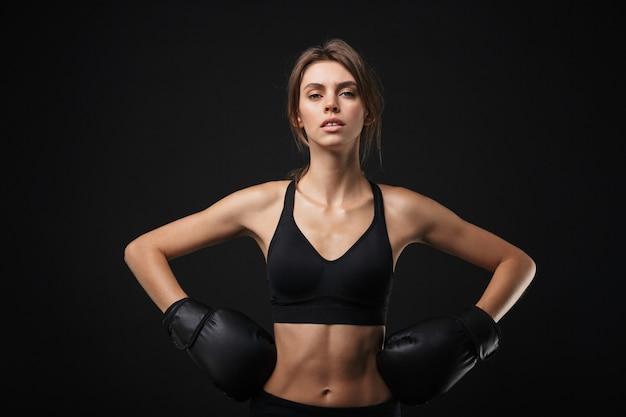Retrato de mujer caucásica femenina en ropa deportiva posando a la cámara con guantes de boxeo durante el entrenamiento en el gimnasio aislado sobre fondo negro