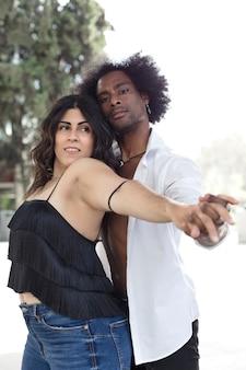 Retrato de mujer caucásica y hombre negro bailando tomados de la mano