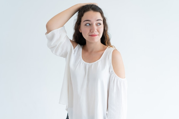 Retrato de la mujer caucásica joven sonriente que rasguña la cabeza