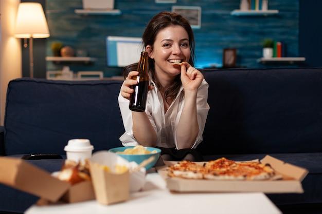 Retrato de mujer caucásica mirando a la cámara sosteniendo la botella de cerveza en las manos