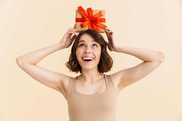 Retrato de mujer caucásica optimista de 20 años vestida con ropa casual sonriendo mientras sostiene la caja presente aislada
