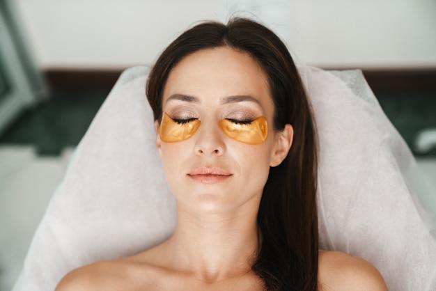 Retrato de mujer caucásica relajada recibiendo procedimiento cosmético con parches en salón de belleza