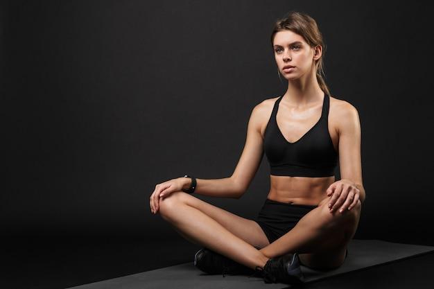Retrato de mujer caucásica seria en ropa deportiva sentado y descansando sobre la colchoneta después del entrenamiento en el gimnasio aislado sobre fondo negro