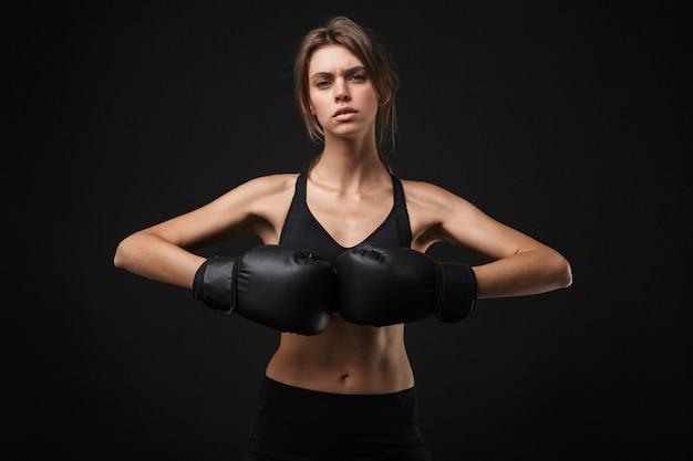 Retrato de mujer caucásica tensa en ropa deportiva posando a la cámara con guantes de boxeo durante el entrenamiento en el gimnasio aislado sobre fondo negro