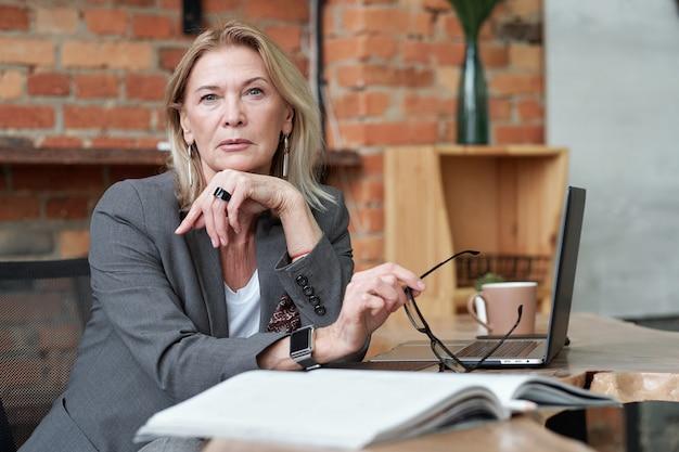 Retrato de mujer ceo seria con reloj inteligente sentado en una mesa y sosteniendo anteojos