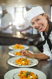 Retrato de mujer chef adornar plato de comida